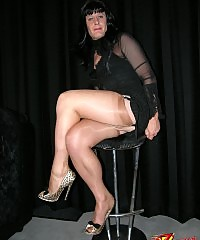 Black haired crossdressing beauty in sleek black dress